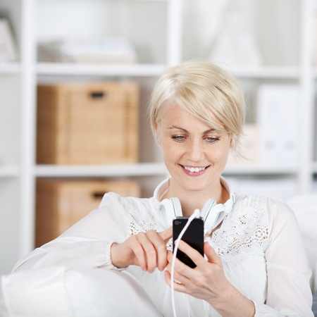 pretty woman with mobile phone and headphones sitting on sofa photo