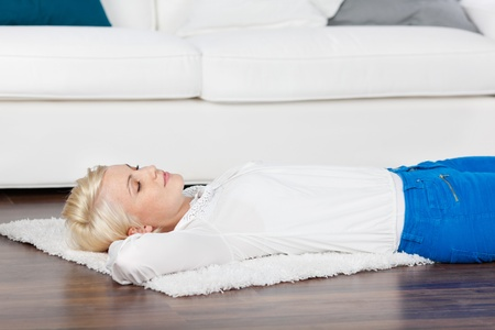 lying on back: young blonde woman lying on wooden floor in the living room