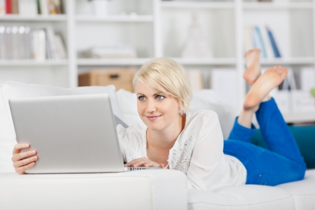 lying on stomach: woman with laptop lying relaxed on sofa at home