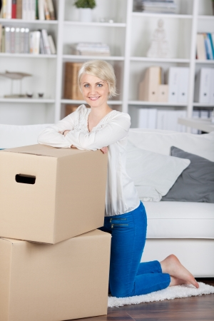 packing boxes: smiling woman leaning on cardbord boxes at home