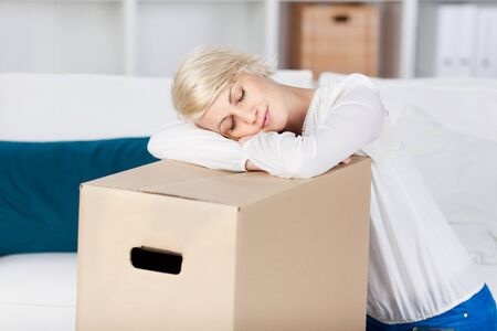 Beautiful young woman resting head on cardboard box in the living room at home photo