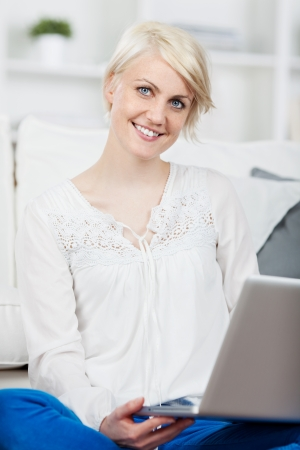 Cute thoughtful young woman sitting on couch with laptop at home photo