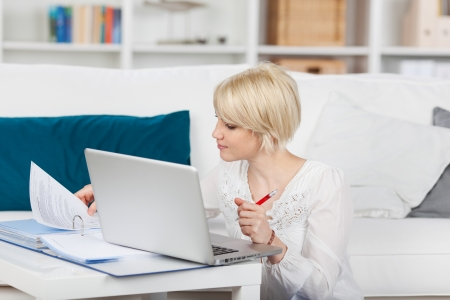 Young blond woman with file folder and laptop at home Фото со стока