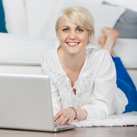 relaxed woman with laptop lying on the floor in living-room photo