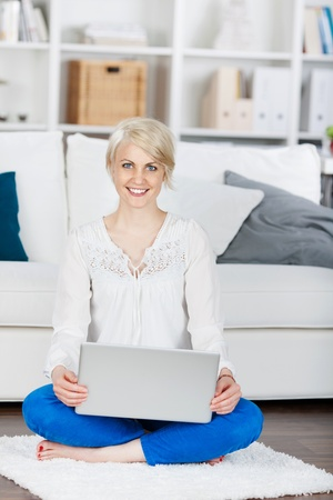 smiling woman with laptop sitting on floor with crossed legs photo