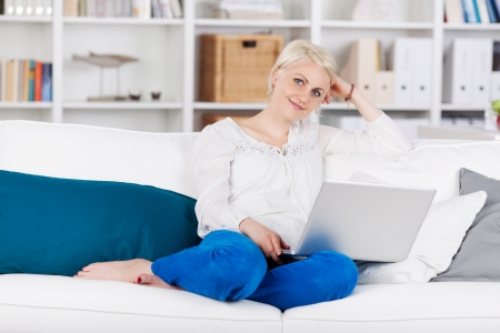 Portrait of a relaxed young woman sitting with laptop on sofa at home photo