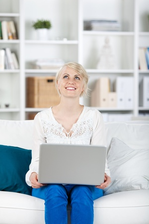 portrait of a happy woman with laptop on sofa looking up photo
