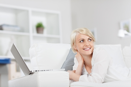 smiling woman with laptop looking to side at home photo
