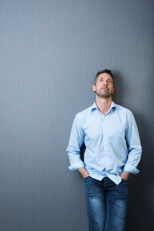 worried executive: Thoughtful mature businessman with hands in pockets looking up against blue wall
