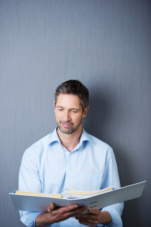 Portrait of mature businessman reading in white binder against blue wall photo