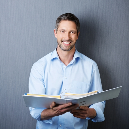 Portrait of mature businessman holding binder against blue wall