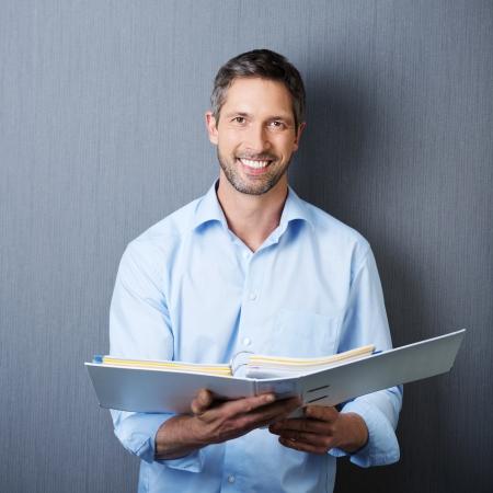 Portret van volwassen zakenman bedrijf bindmiddel tegen de blauwe muur Stockfoto