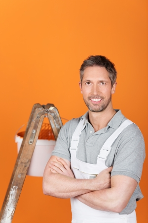 Portrait of confident male painter with arms crossed photo