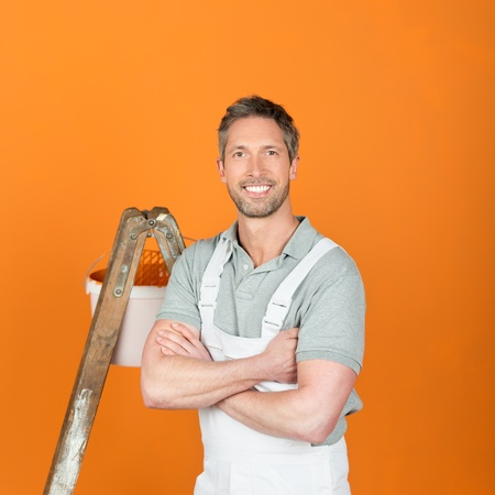 Portrait of smiling male painter with arms crossed standing against orange painted wall photo