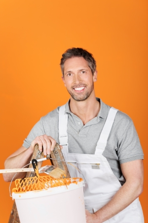 redecorating: Portrait of happy smiling male painter against orange painted wall Stock Photo