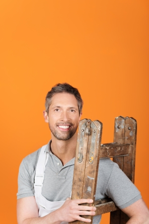 Portrait of confident male painter carrying wooden ladder photo