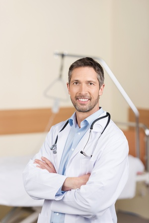 Portrait of confident mature doctor with arms crossed standing in hospital photo