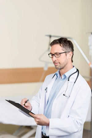admission: Portrait of confident mature doctor holding clipboard in hospital Stock Photo