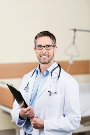 Portrait of smiling mature doctor with clipboard in hospital photo