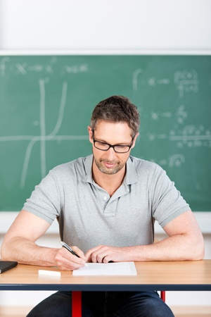 tertiary: Male thoughtful teacher checking examination papers at bench in classroom