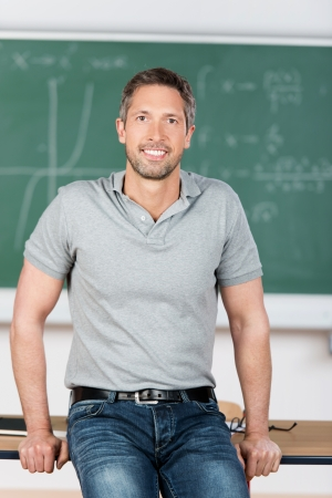 Portrait of confident mature teacher leaning on bench in classroom photo