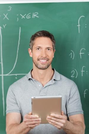 Portrait of smiling male teacher holding digital tablet against chalkboard in classroom photo