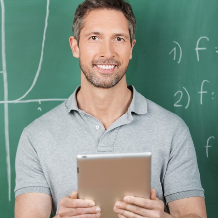 Portrait of confident male teacher holding digital tablet against chalkboard in classroom photo
