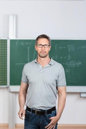 tertiary: Portrait of confident mature teacher standing in classroom