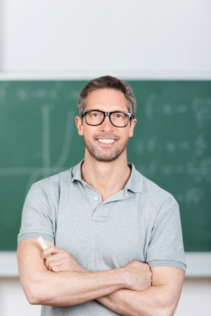 Portrait of confident mature teacher with arms crossed standing in classroom