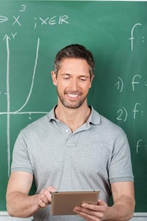 Happy male teacher using digital tablet against chalkboard in classroom photo