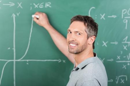 tertiary: Mature male teacher writing on chalkboard in classroom Stock Photo
