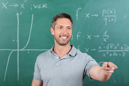 Mature male teacher pointing while looking away against chalkboard photo