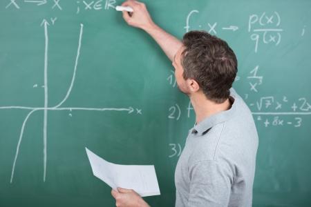 Achteraanzicht volwassen mannelijke leraar bedrijf papier tijdens het schrijven op krijtbord in de klas