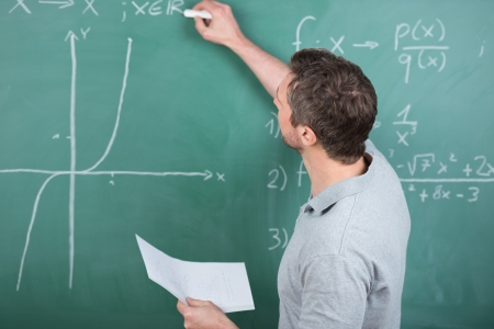 secondary school teacher: Rear view mature male teacher holding paper while writing on chalkboard in classroom