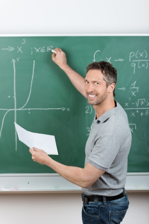 Mature male teacher holding paper while writing on chalkboard in classroom photo