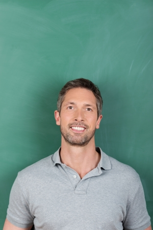 Smilling mature male teacher against blank green blackboard photo