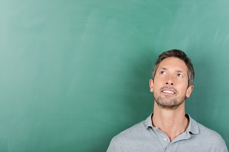 Thoughtful mature male teacher against blank blackboard - copy space for text photo