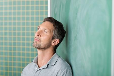Pensativo guapo profesor de sexo masculino maduro contra la pizarra en blanco