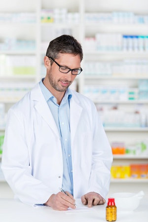 Mature male pharmacist writing prescription on paper at pharmacy counter photo