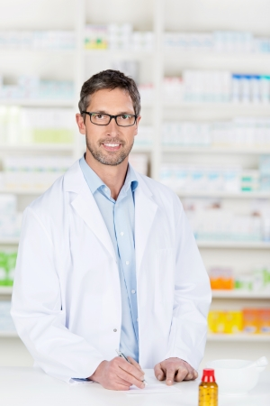 Mature confident male pharmacist at pharmacy counter Stock Photo - 21111929