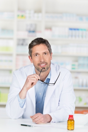 Thoughtful mature male pharmacist holding glasses at pharmacy counter photo