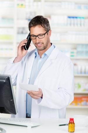 Mature male pharmacist using phone at pharmacy counter photo