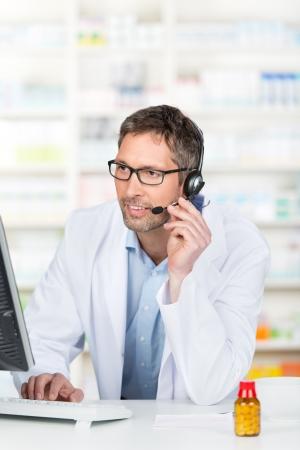 drugstore: Farmacéutico masculino maduro con auriculares mientras se usa el ordenador en mostrador de la farmacia Foto de archivo