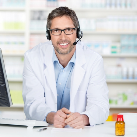 telephonic: Mature male pharmacist wearing headset at pharmacy counter