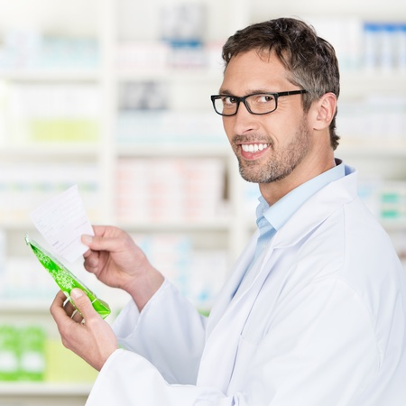 Portrait of mature male pharmacist holding prescription paper and product in pharmacy photo