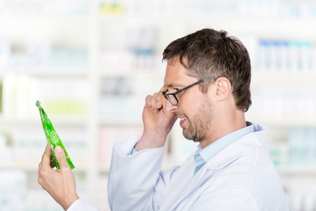 Portrait of mature male pharmacist holding product in pharmacy photo