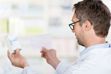 Closeup of mature male pharmacist reading prescription paper and medicine details in pharmacy photo