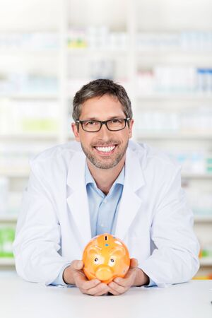 Portrait of happy male pharmacist holding piggybank at pharmacy counter photo