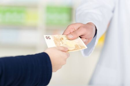 medical bill: Cropped image of customers hand passing money to male pharmacist in pharmacy Stock Photo