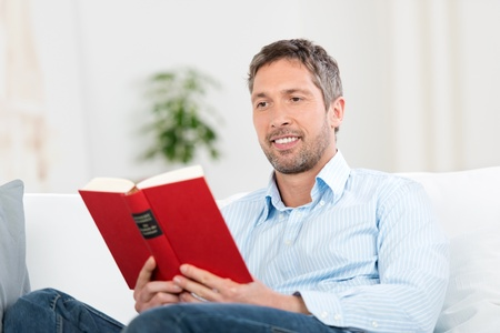 leisureliness: Handsome mature man reading book in house
